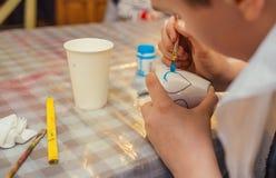 Мальчик держа щетку в его руках и украшая чашку стоковая фотография rf