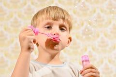 Мальчик дует пузыри мыла, конец-вверх стоковое изображение
