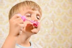 Мальчик дует пузыри мыла, конец-вверх стоковое фото rf