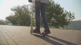 Мальчик едет скутер в парке Камера двигает за акции видеоматериалы