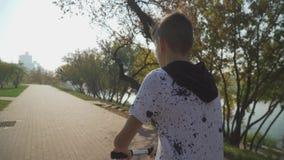 Мальчик едет скутер в парке Камера следовать за ребенк видеоматериал