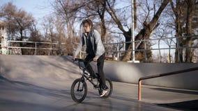 Мальчик едет фокусы BMX задействуя в парке скейтборда на солнечный день Хобби, воссоздание, жизнь спорта сток-видео
