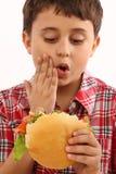 мальчик есть гамбургер Стоковая Фотография