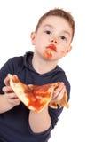 мальчик есть детенышей пиццы Стоковое Изображение RF