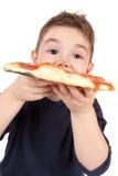 мальчик есть детенышей пиццы Стоковая Фотография RF