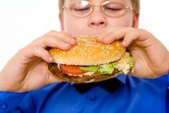мальчик есть детенышей школы гамбургера Стоковые Фотографии RF