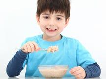 мальчик есть oatmeal стоковая фотография