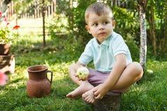 Мальчик ест зеленое яблоко сидя на пне дерева Активный мальчик есть зеленое яблоко стоковое фото rf