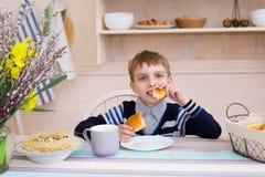 Мальчик ест круассан в завтраке Стоковое фото RF