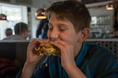 Мальчик ест staisfied большой бургер Стоковые Фотографии RF