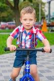 Мальчик ехать езда велосипеда с его языком вне в парке Стоковое Изображение RF