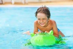 Мальчик ехать раздувная игрушка в бассейне Стоковые Изображения RF