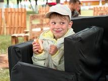 Мальчик жадно есть цыпленка с его руками стоковая фотография rf