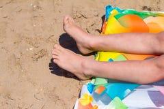 Мальчик загорая на пляже лежа на концепции каникул пляжа солнца моря ног песка видимой только стоковое фото rf