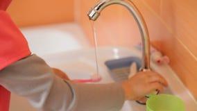 Мальчик закрывает кран с водой акции видеоматериалы