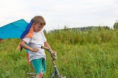 Мальчик запускает в голубое небо змея Стоковое фото RF