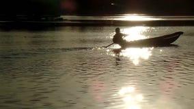 Мальчик зарабатывает прожитие как рыболов в озере используя шлюпку Силуэты видеоматериал