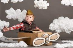 Мальчик играет в самолете сделанном картонной коробки и мечт быть пилотом, облаками ваты на серой предпосылке Стоковые Изображения