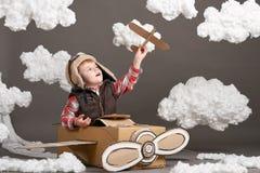 Мальчик играет в самолете сделанном картонной коробки и мечт быть пилотом, облаками ваты на серой предпосылке Стоковые Фотографии RF