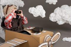 Мальчик играет в самолете сделанном картонной коробки и мечт быть пилотом, облаками ваты на серой предпосылке Стоковое Фото