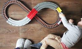 Мальчик играет железную дорогу детей Мама наблюдает ее сына сверху Ребенок fascinated поездом стоковое изображение