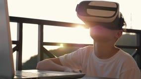 Мальчик играет на компьютере в стеклах виртуальной реальности в заходе солнца на заходе солнца Концепция современного