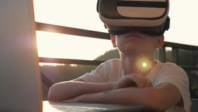 Мальчик играет на компьютере в стеклах виртуальной реальности в заходе солнца на заходе солнца Концепция современного акции видеоматериалы