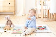 Мальчик играет с деревянными игрушками и показывает 2 Воспитательные деревянные игрушки для ребенка Портрет мальчика сидя на поле стоковые фото