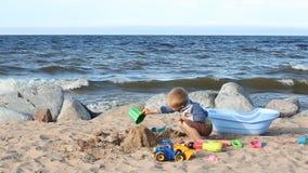 Мальчик играет с песком и груши на океане подпирают сток-видео