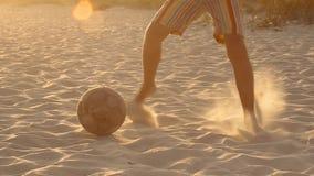 Мальчик играет футбол в песке сток-видео