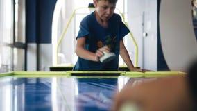 Мальчик играет хоккей воздуха с его отцом Взгляд вдоль таблицы игры Развлечения видеоматериал