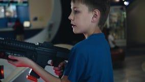 Мальчик играет эмоционально в зале торгового автомата В его руках винтовка игры Большие важные персоны Эмоции детей сток-видео
