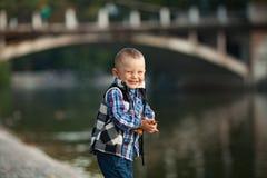 Мальчик играющ и держащ листья осени в его руках d стоковое изображение