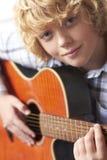 Мальчик играя акустическую гитару Стоковые Изображения