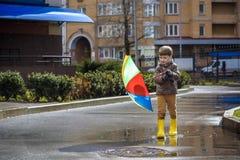 Мальчик играя в ненастном парке лета Ребенок при красочный зонтик радуги, водоустойчивое пальто и ботинки скача в лужицу и грязь Стоковая Фотография RF