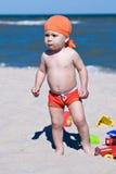 Мальчик играя в песке на пляже Стоковые Изображения