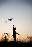 Мальчик играя змея на silhouetted луге захода солнца лета Стоковое Фото