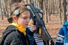Мальчик играя игру гужа лазера outdoors и смотря расстроенный Стоковое Изображение RF