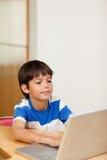 Мальчик играя компютерные игры на компьтер-книжке Стоковые Изображения RF