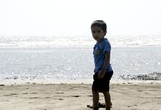 Мальчик играя на песке пляжа стоковые изображения