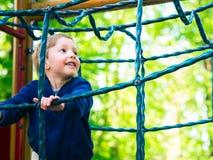 Мальчик играя на спортивной площадке активизма стоковые фотографии rf