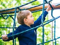 Мальчик играя на спортивной площадке активизма стоковые фото