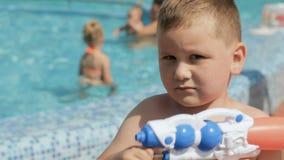 Мальчик играя около бассейна с водяным пистолетом акции видеоматериалы