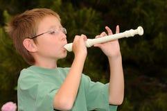 мальчик играя рекордера стоковое фото rf
