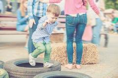 Мальчик играя скача автошины на фестивале улицы Стоковое фото RF