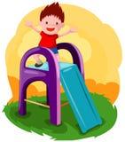 мальчик играя скольжение Стоковое Фото