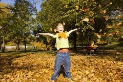 Мальчик играя снаружи с цветастыми листьями Стоковое Фото