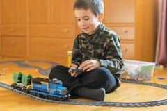Мальчик играя с железной дорогой игрушки Мальчик играя с железной дорогой лежа на поле Радостные эмоции стоковые фото