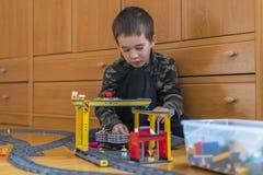 Мальчик играя с железной дорогой игрушки Мальчик играя с железной дорогой лежа на поле Радостные эмоции стоковые изображения