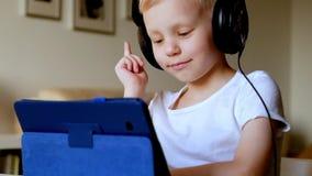 Мальчик играя с наушниками ПК таблетки нося видеоматериал
